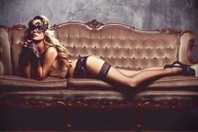 Escort in sexy Dessous auf einer Couch in der Villa Aminta