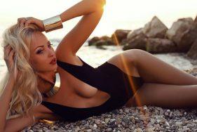 Blondes Escort Girl liegt am Strand von Paxos