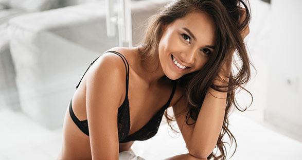 Asiatisches Escort in der sexy Dessous auf dem Bett