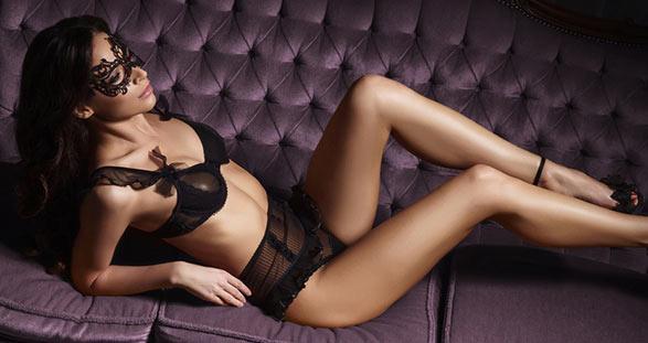 Teilzeit Escort in sexy Dessous auf dem Sofa