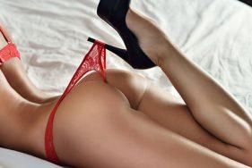 Escort Girl liegt auf dem Bett in roten Dessous